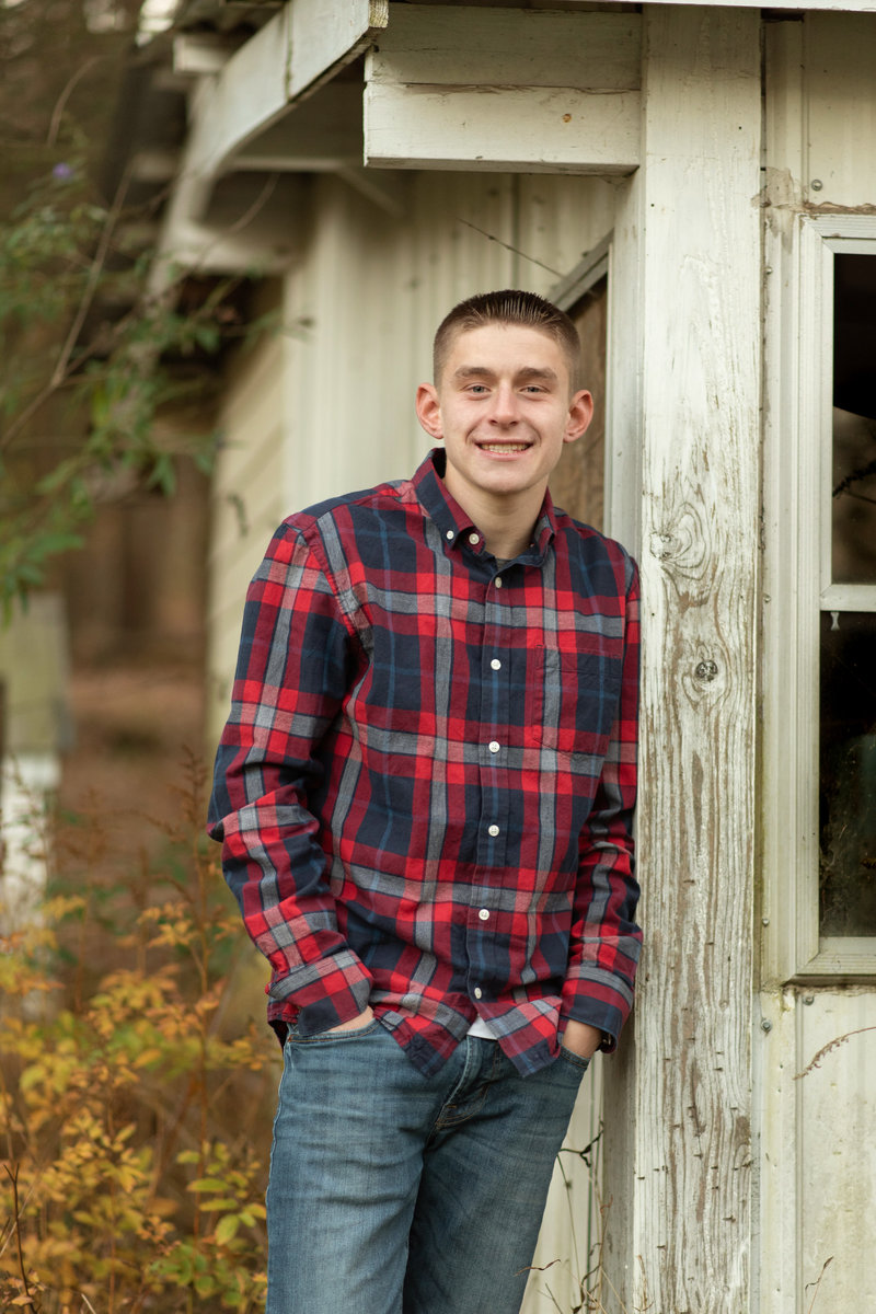 Senior boy in flannel leaning against wooden shed