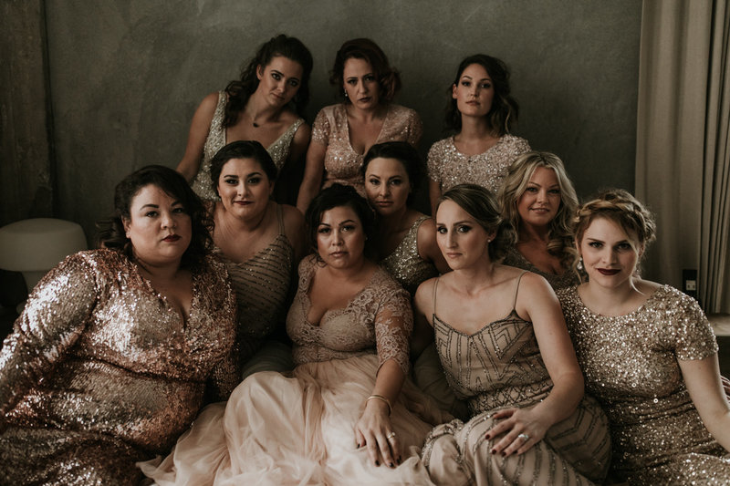 Bride and bridesmaids in gold metallic dresses posing for a Vogue inspired wedding party portrait shot at this Natural History Museum wedding on New Years Eve