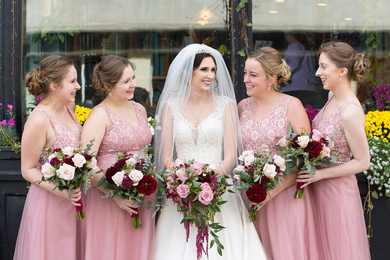 bridesmaids in light pink dresses smiling outside of cityflats port huron