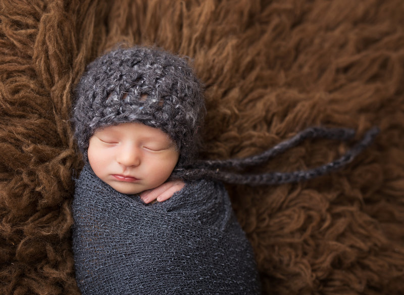 boy wrapped in grey on brown flokati