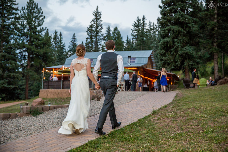 Bride and Groom Walk hand in hand to wedding reception at Mountain View Ranch