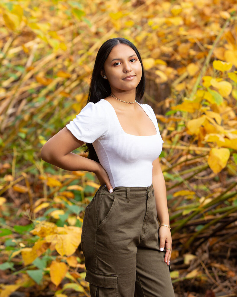 senior portrait girl posed in front of yellow leaves