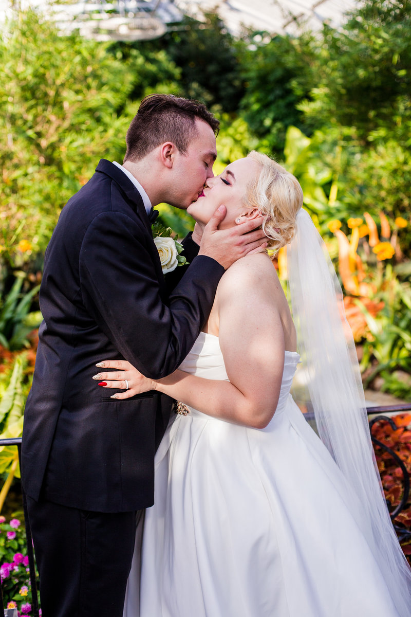 Bride and groom kissing in the Phipps Conservatory