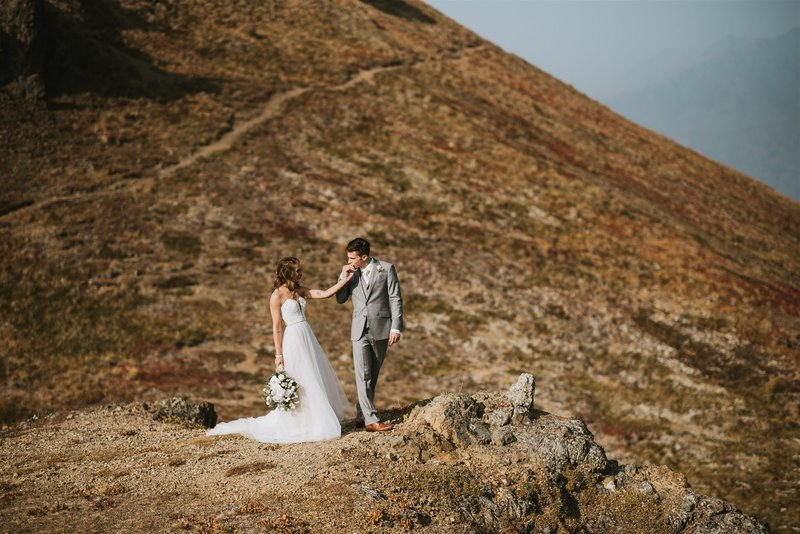 couple walking out on cliff over fall mountains as groom kisses the brides hand at arctic valley