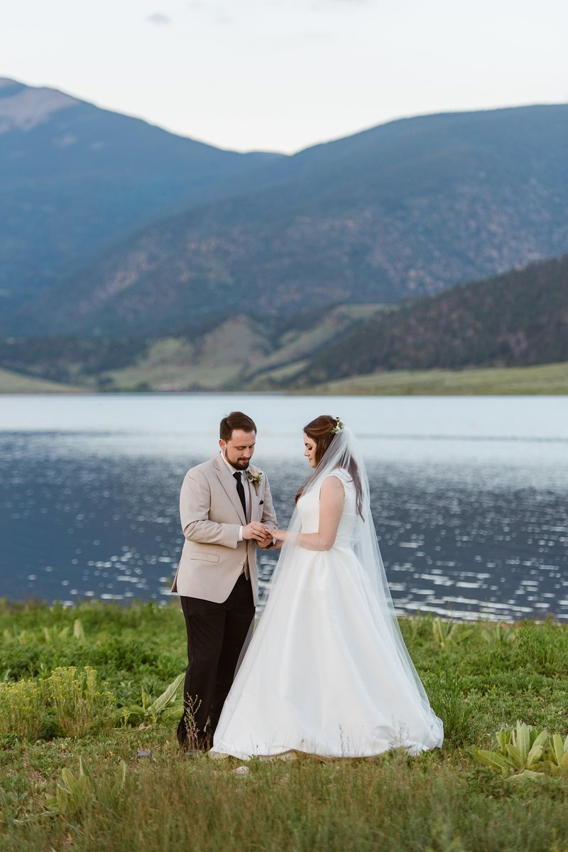 Couple exchanges wedding ring at their Eagle Nest Lake elopement in the northern New Mexico mountains.