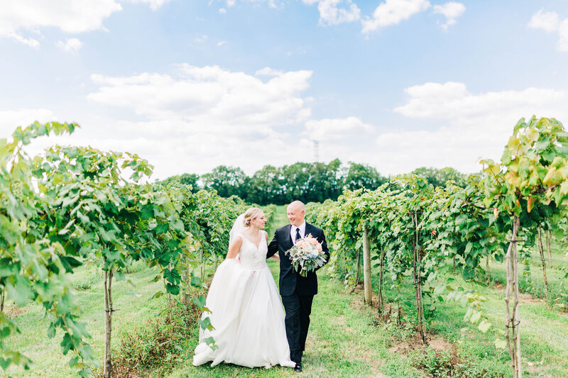 August wedding couple walks through vineyard at Sycamore At Mallow Run