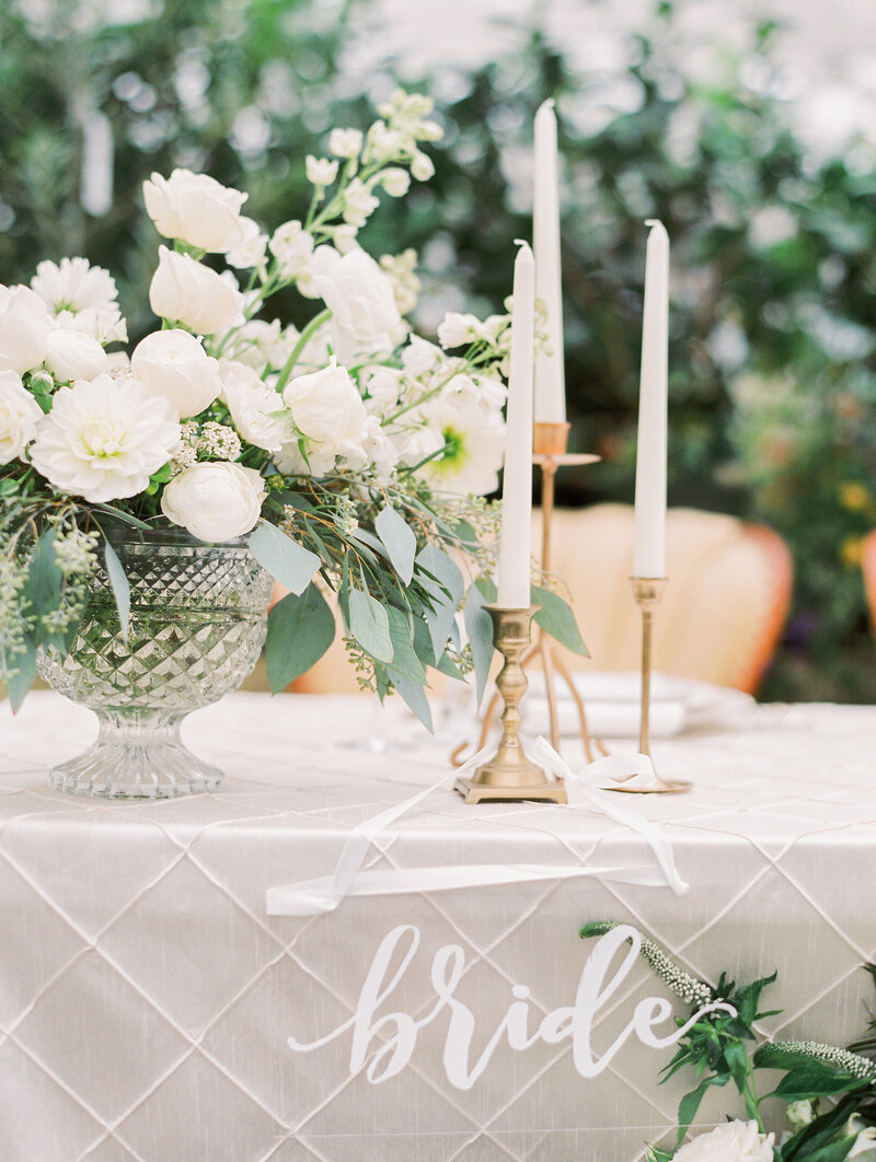 table with white candles and flowers with a bride sign on it
