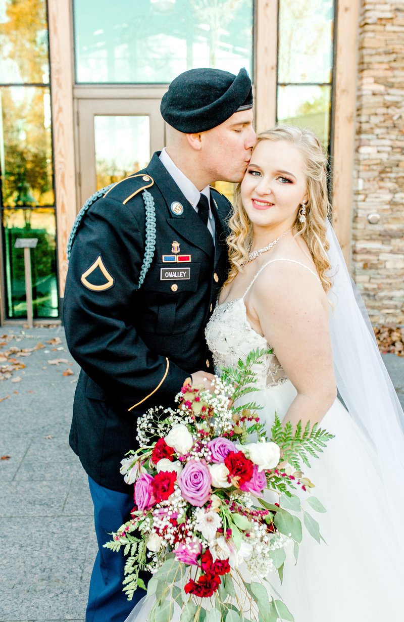 Military groom kissing bride with colorful bouquet at Quantico Marine Corps Base wedding