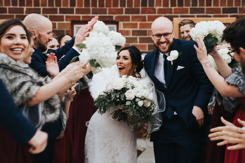 A wedding party surround an excited bride and groom and share high fives and handshakes
