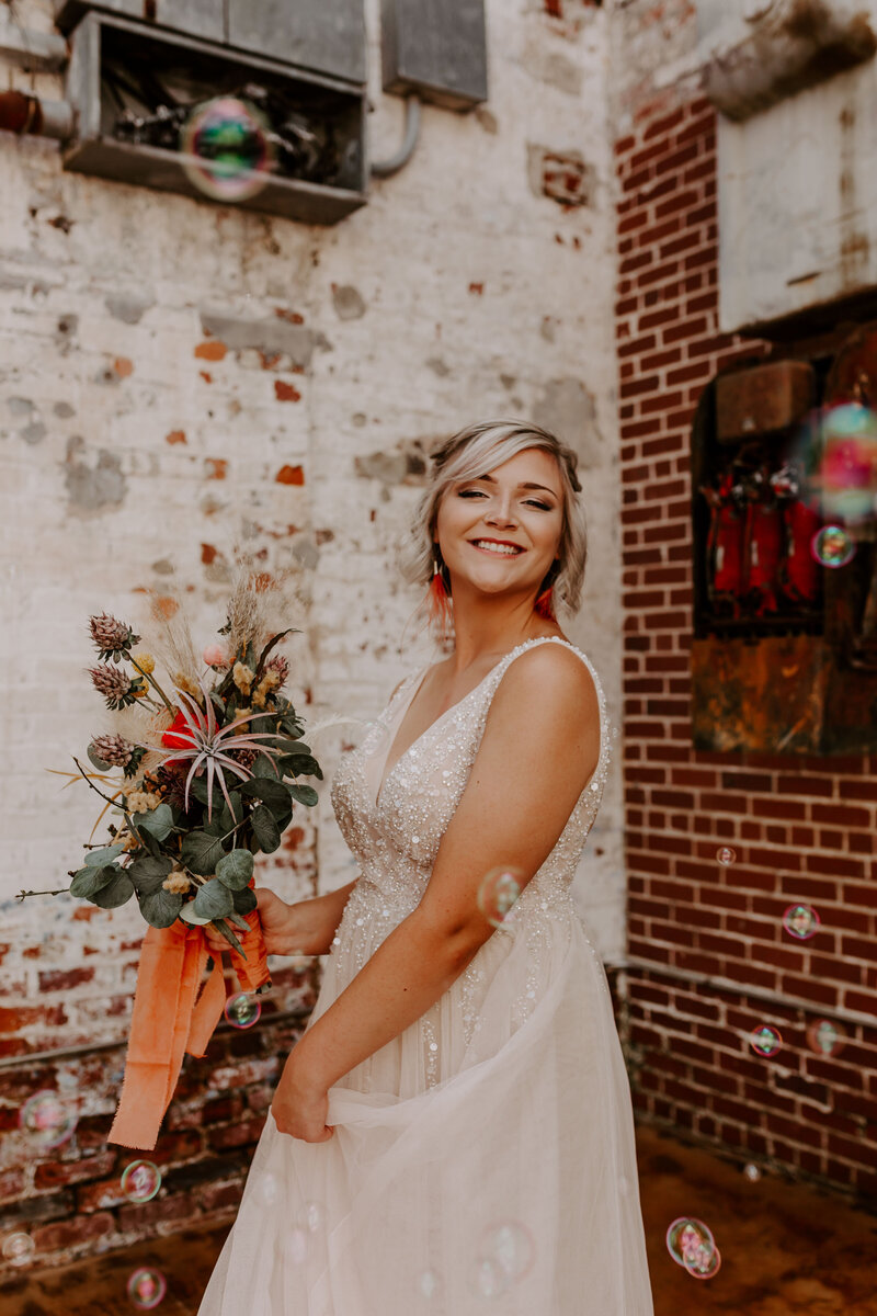 bride twirling in her dress with boho bouquet