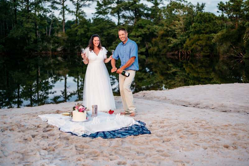 groom opening champagne by the water