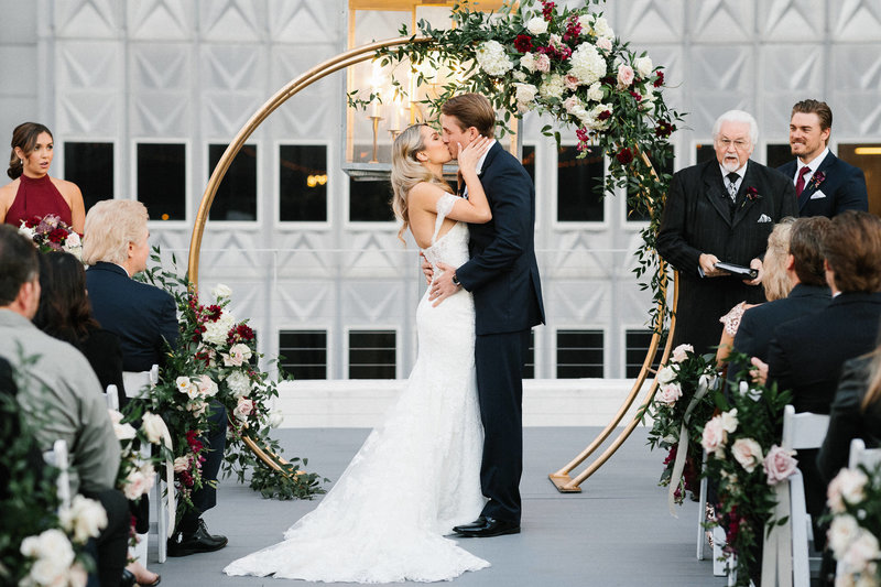 bride and groom kissing  during wedding ceremony in front of floral arch