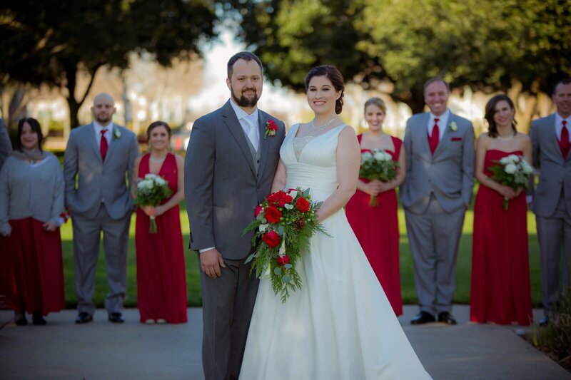 Sacramento wedding photography of bride and groom posed in front of bridal party with everyone smiling looking at the camera.