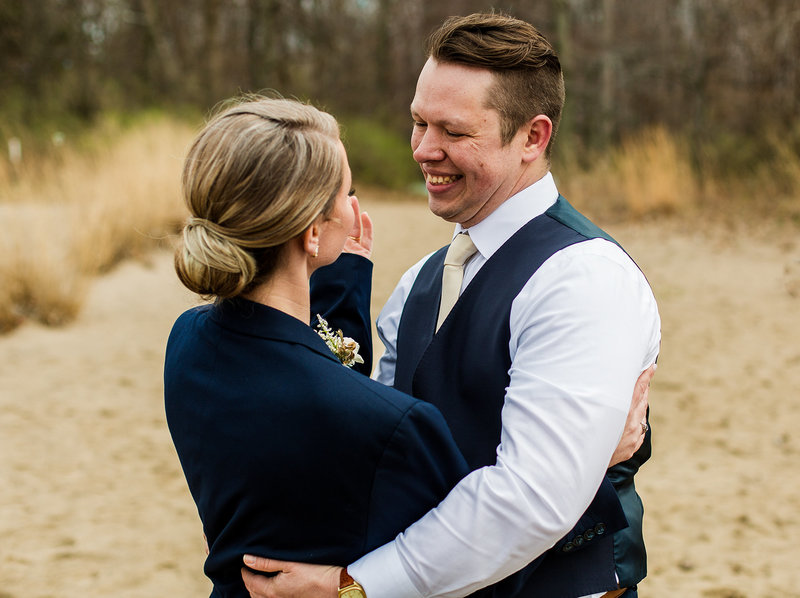 Groom smiles at bride after their Presque Isle Beach wedding