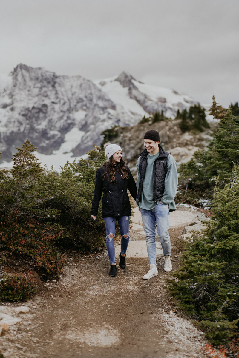 Husband and Wife walk a path at scenic outlook Mt. Baker in Washington state.