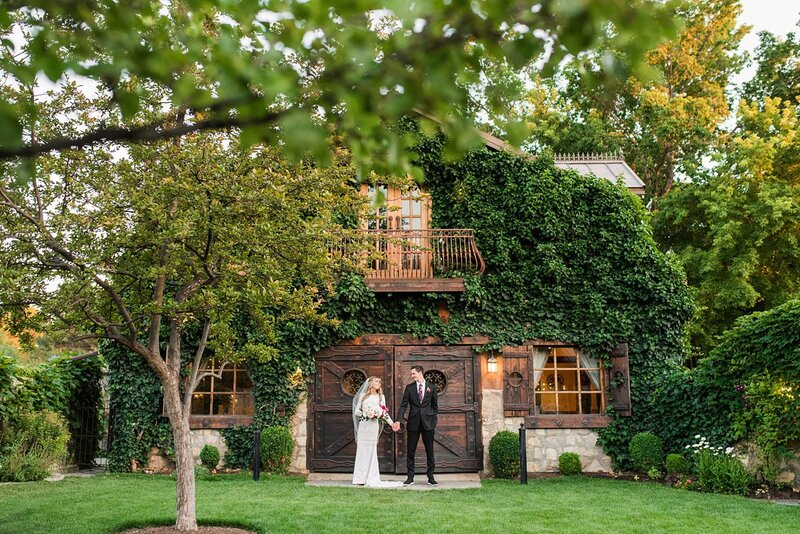 Bride and groom in front of barn at Wadley Farms