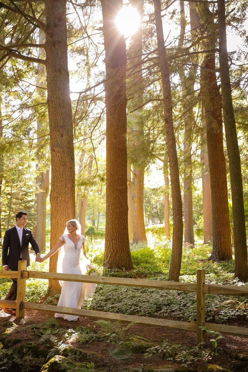 Bride and groom walking in a forest with great light