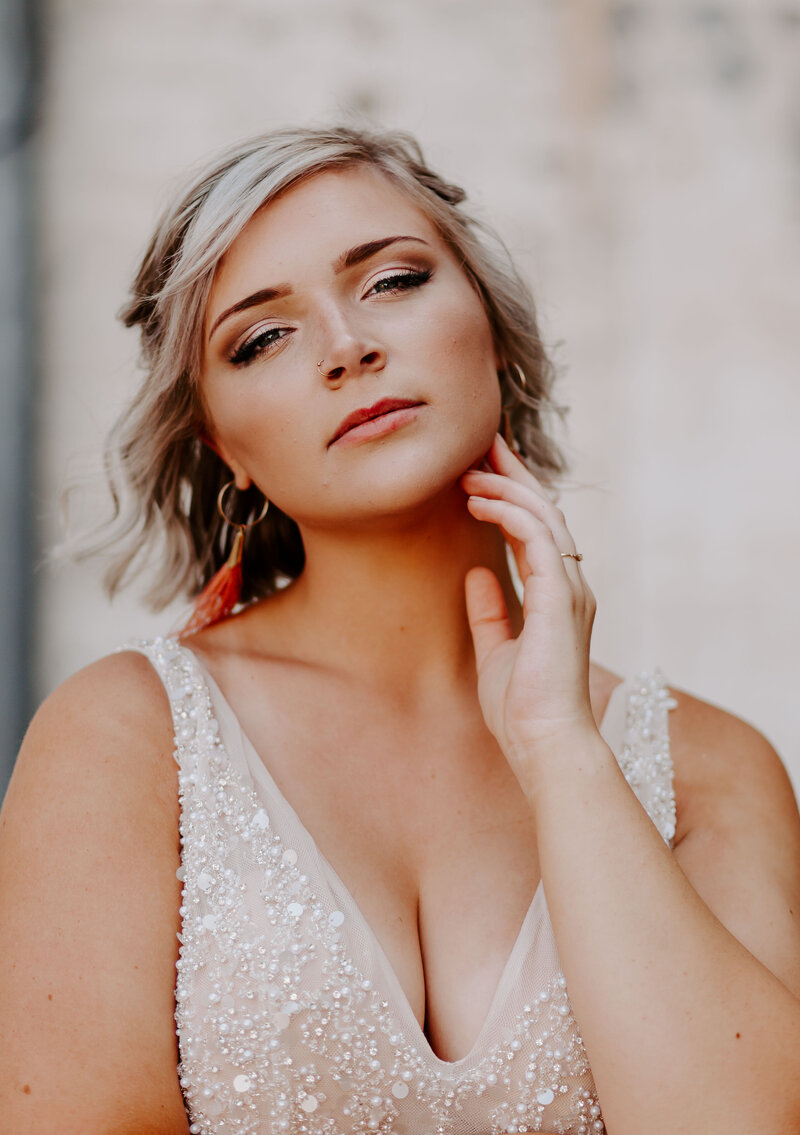 Bride looking at camera with her hand on her neck