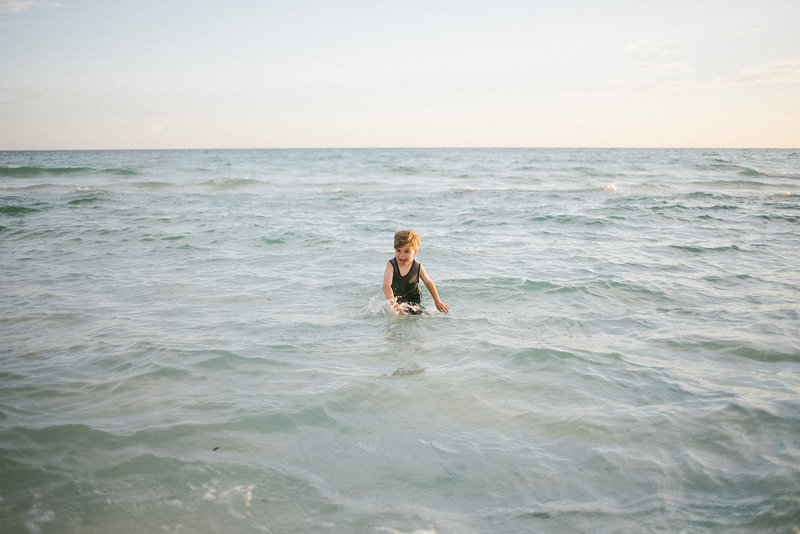 Little boy waste deep in the ocean during family vacation, captured by Laurie Baker