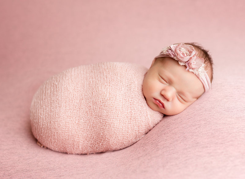 Baby wrapped in dusty rose colored blanket