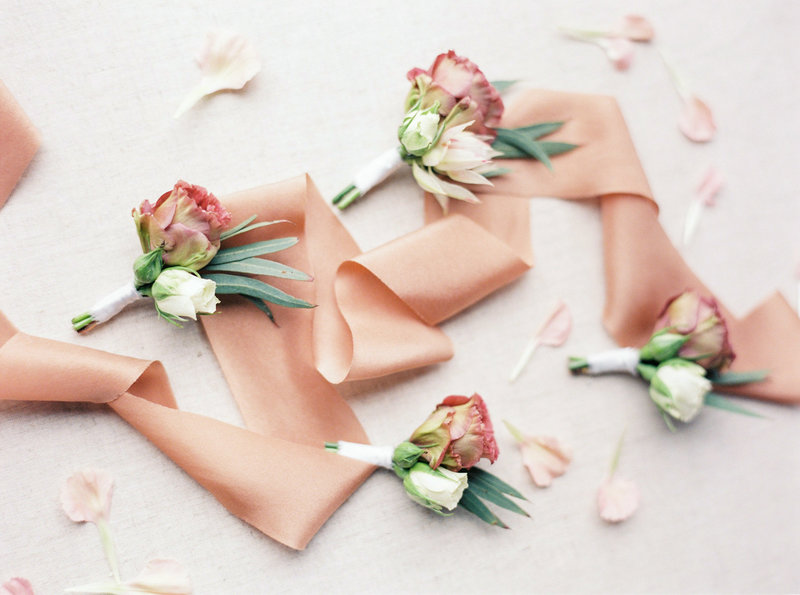 Flatlay styling with buttonieres, silk ribbon and flower petals