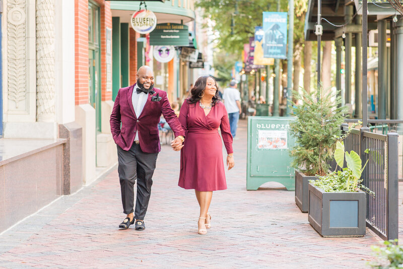 bride and groom enjoying a stroll down street during their downtown memphis tennessee engagement session