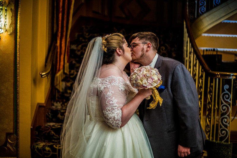 Bride and groom kissing at the bottom of a staircase at the Warner Theatre