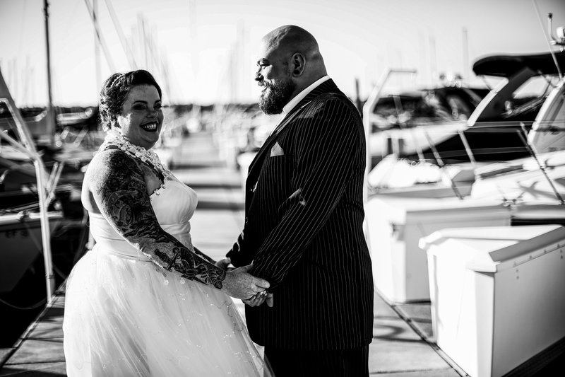 Bride and groom hold hands next to some boats at the Erie Yacht Club