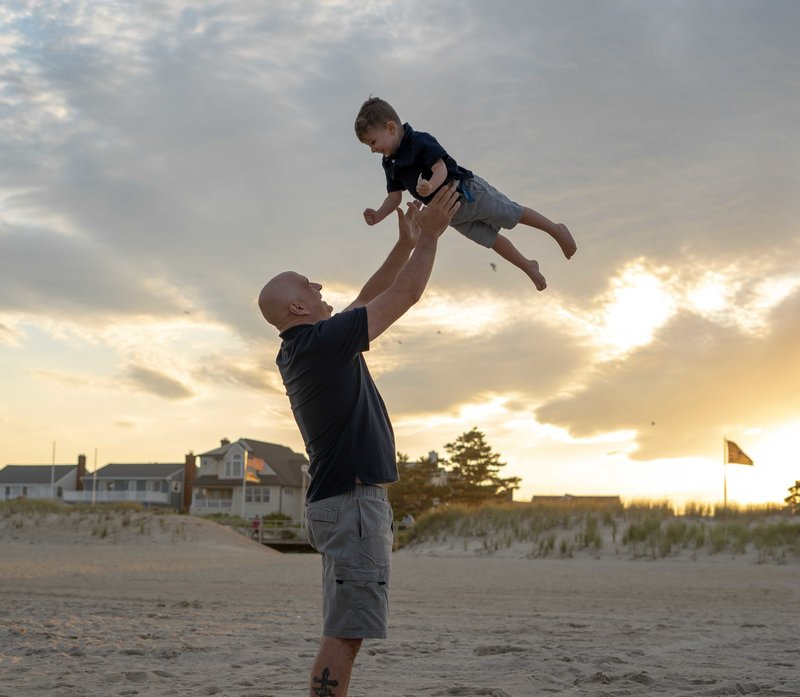 Mike holding Aaron in the air playing on the beaech
