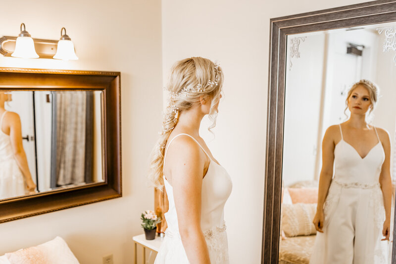 "alt=""bride looking in mirror at bridal suite"""