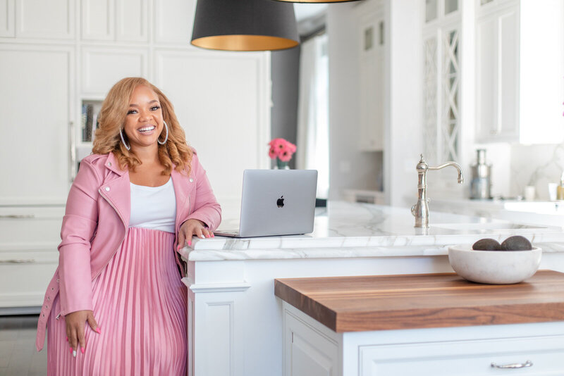 african american woman in pink jacket leans arm on kitchen counter next to a grey macbook pro laptop