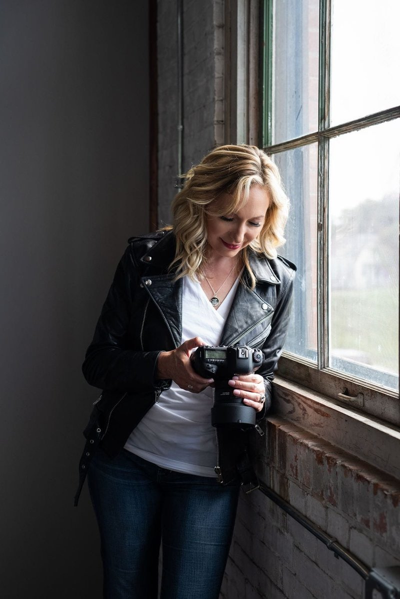 Jen Denton holding a camera looking at the back of it standing next to a window