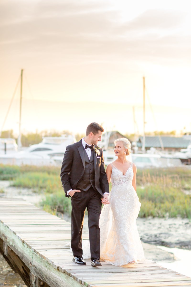 A bright and colorful sunset stains the sky behind a bride and groom walking on a dock with the charleston harbor behind them at the charleston wedding venue historic rice mill