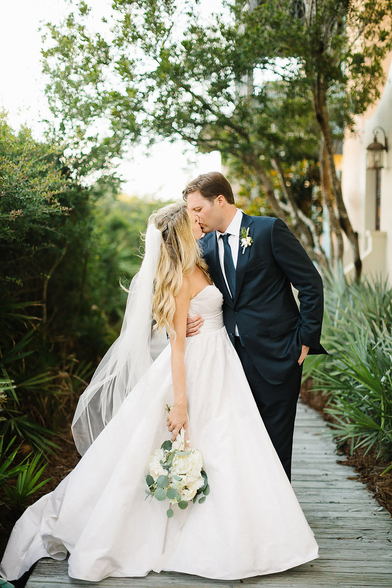 bride and groom kiss embrace  rosemary beach wedding