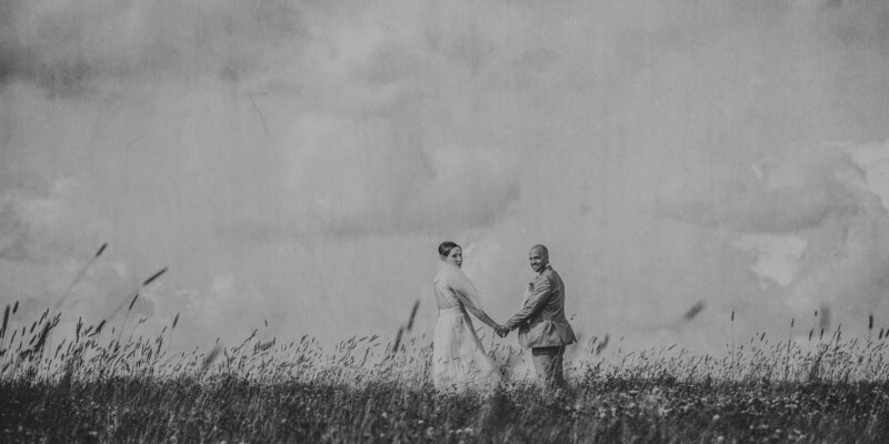 bride and groom  on hilltop of wild grasses
