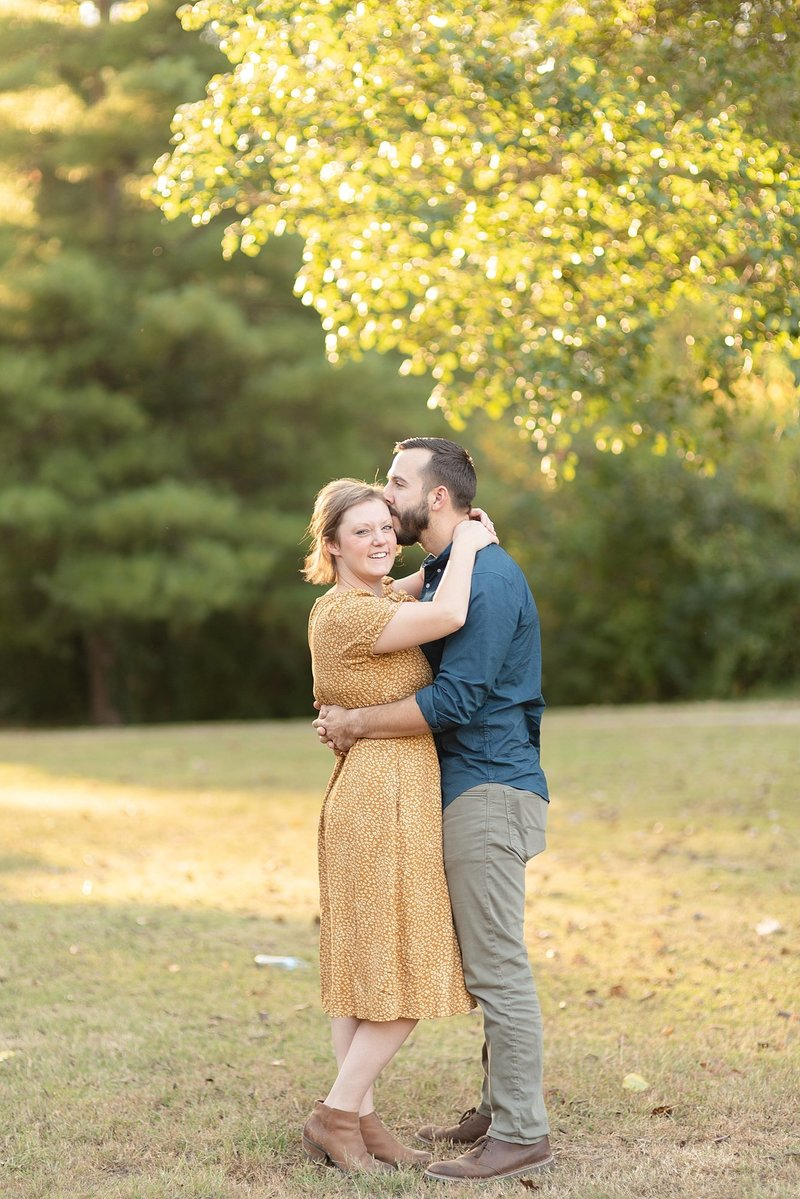 A husband and wife are nuzzling eachother and hugging eachother for family portraits in Green Hills Nashville Tennessee by Family photographer Dolly DeLong Photography