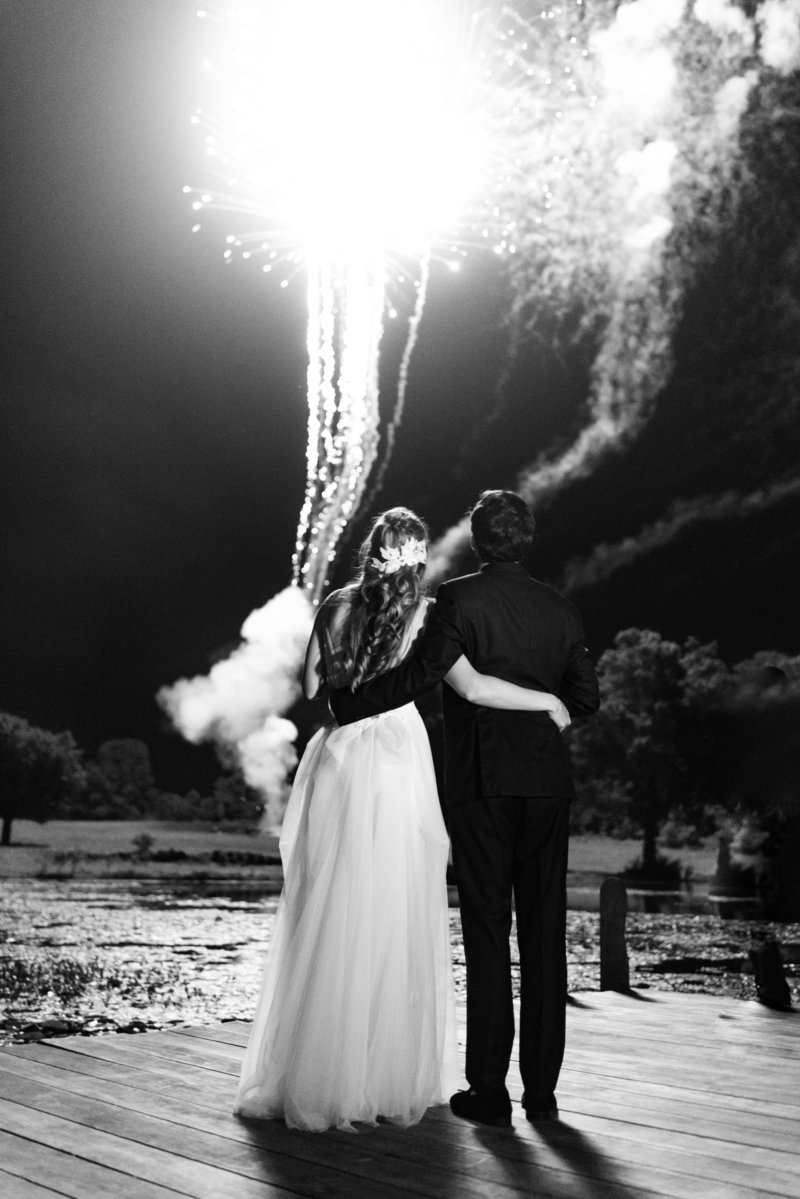 Bride and groom hugging and looking over wedding fireworks in Middleburg Virginia Wedding