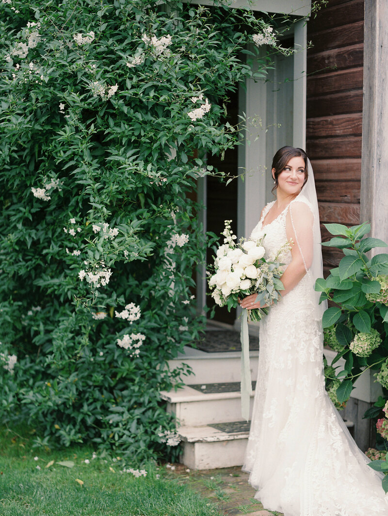 bride holding wedding bouquet and looking off over her shoulder and smiling