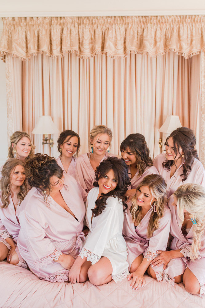 bridesmaids on bed in bridal suite at great marsh estate wedding in northern virginia by costola photography