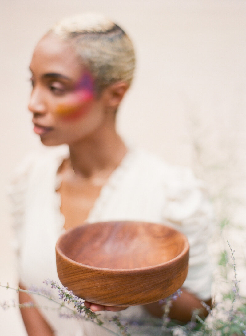 Beautiful African American woman holds handcrafted wooden bowl
