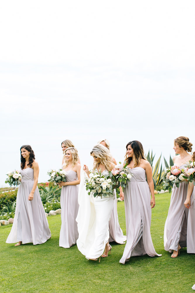 bride with bridemaids on wedding day in laguna beach