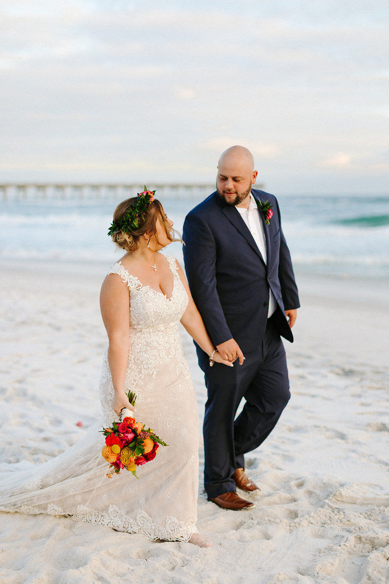 bride and groom walking on beach during sunset