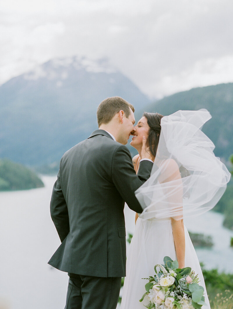 Bride smiles with veil blowing in wind on a mountain top while groom leans in for a kiss at Diablo Lake in Washington
