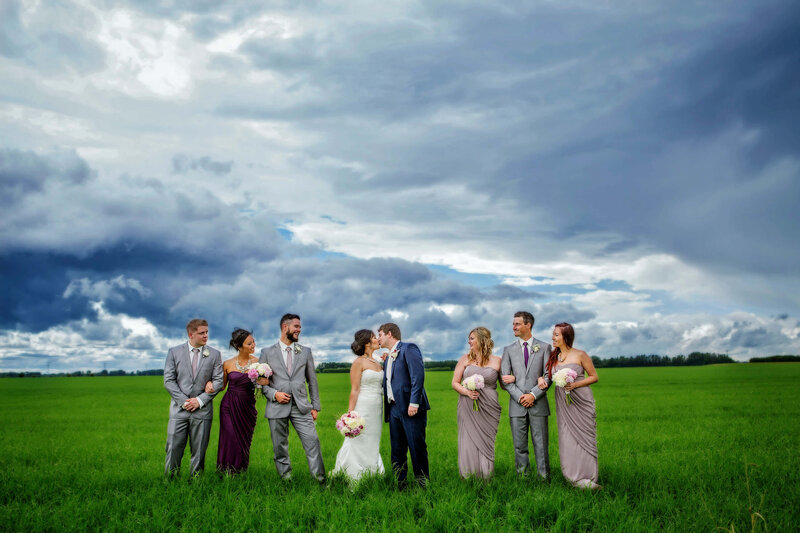 wedding party in vibrant grass and moody sky
