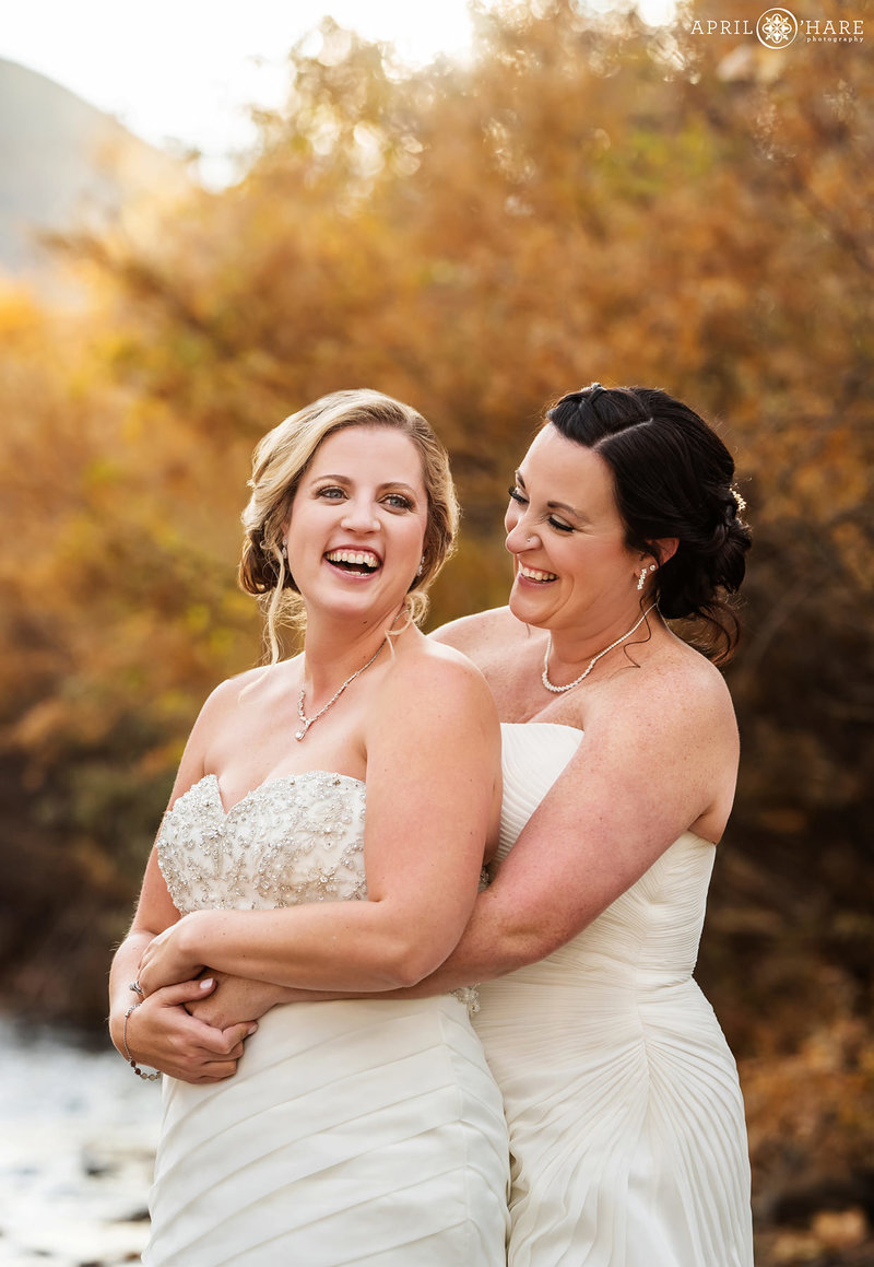 Brides laugh together on their same sex wedding day on a pretty autumn day at the Golden Hotel
