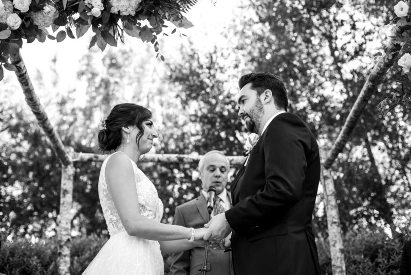 Black and white image of bride and groom looking at each other at sweetheart table