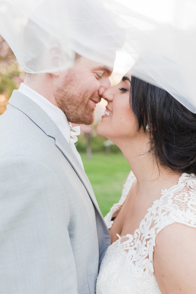 bride and groom kissing under veil  at Stone House at Stirling Ridge Maryland Wedding by  Costola Photography