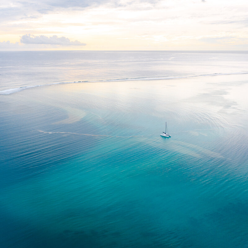 Aerial drone view on Moorea lagoon with the boat in the shade of blue at the sunset during a honeymoon