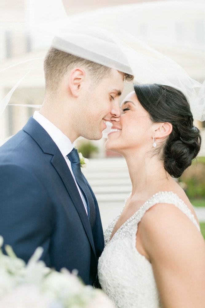 bride and groom kissing under veil at springfield manor winery and distillery wedding by costola photography