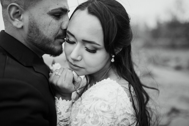 Close up photo of Groom kissing Bride's temple